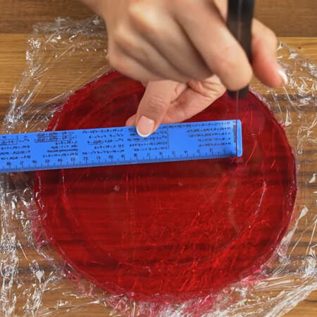 Желе в круглой форме уже застыло, вынимаем его из формы. Получившееся желе нужно разрезать на кольца шириной 2 см. Я сначала сделала метки на желе с помощью линейки через 2 см.