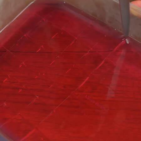 Желе, залитое в прямоугольную форму достаем из холодильника и нарезаем небольшими кубиками.