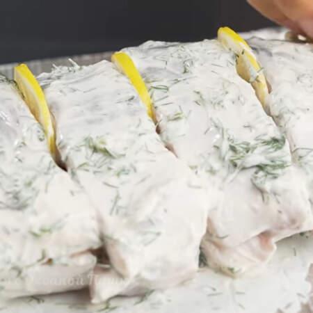 Сверху рыбу смазываем оставшимся соусом. Между кусками рыбы вставляем кружочки лимона.