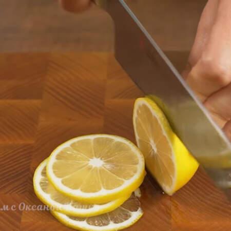 Один лимон разрезаем пополам. Одну половинку лимона откладываем, она понадобится позже, а вторую половинку нарезаем тонкими кружочками.