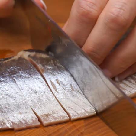 Сначала готовое филе одной сельди, очищенное от кожи и костей, нарезаем порционными кусками. Желательно использовать слабосоленую сельдь.