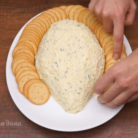 Вокруг начинки красиво выкладываем круглый соленый крекер. Всего понадобится примерно 300 г крекера.