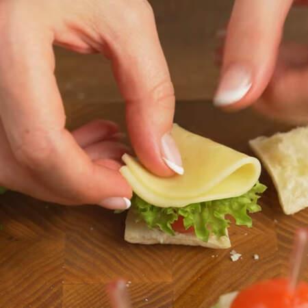 Половинку сыра складываем вдвое и кладем на лист салата.