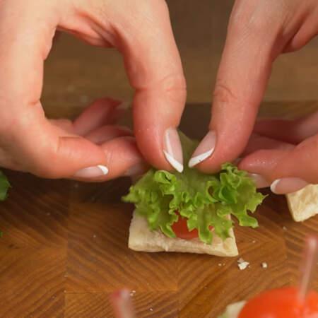 На одну половинку кладем нижнюю часть от помидора.  Сверху помидор накрываем небольшим листиком салата.