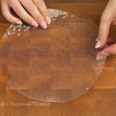 Сразу же кладем ее на доску, пока она не стала мягкой. Пока будем класть начинку, бумага размокнет.