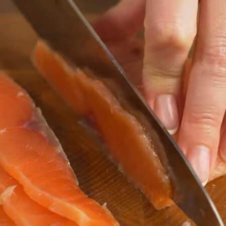 Красную соленую рыбу нарезаем пластинками.