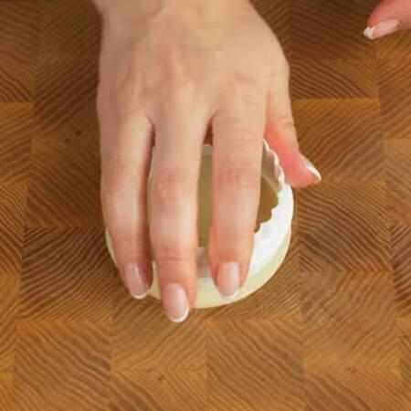 Из сыра уже нарезанного пластинками вырезаем круги, точно такого же диаметра как и основа из хлеба.