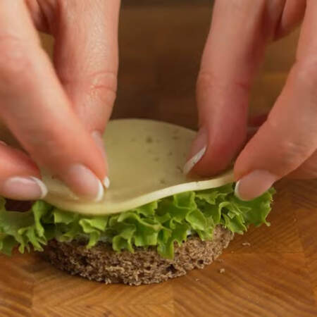 На сыр кладем подготовленный салатный лист. Сверху кружок сыра.