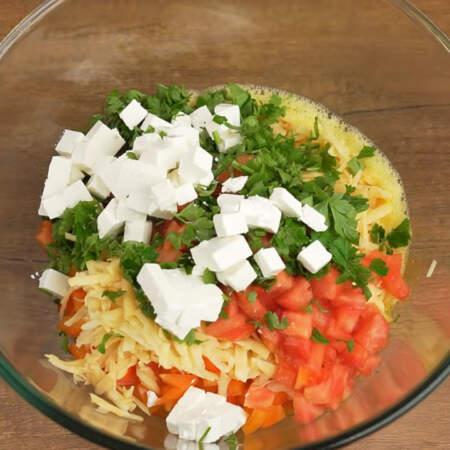 Ко взбитым яйцам насыпаем нарезанный перец, тертый картофель, помидоры, петрушку и кубики сыра фета.