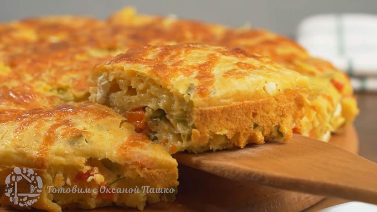 Готовый пирог достаем из формы и разрезаем его на порционные куски и подаем на стол. Закусочный пирог получился вкусным и сытным.