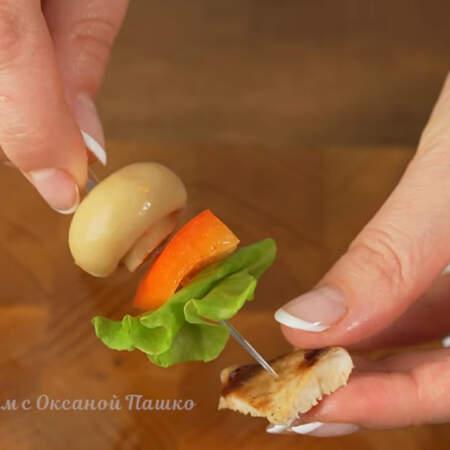 Отрываем кусочек листа салата и складываем в два или три раза. Нанизываем на шпажку листик салата и кусочек индейки.