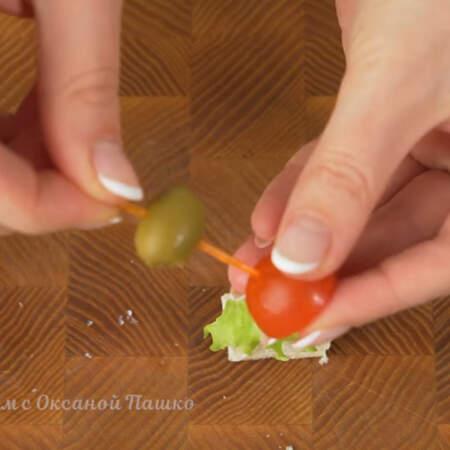 На шпажку нанизываем оливку и половинку помидорчика черри.