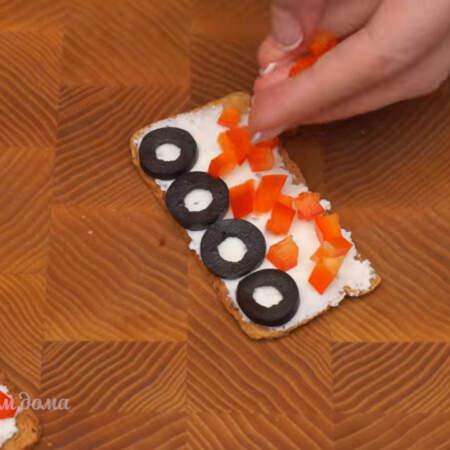 С одной стороны на хлебцы выкладываем несколько кружочков маслин. С другой стороны выкладываем кубики перца.