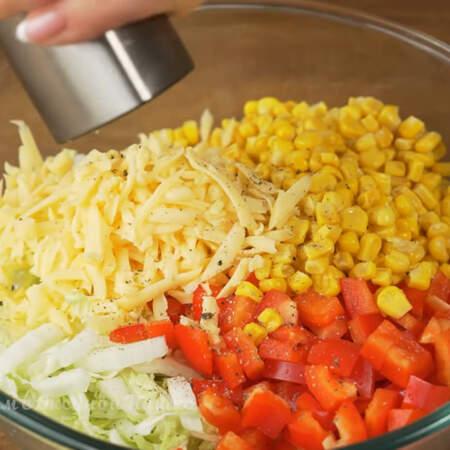 В большую миску кладем подготовленную пекинскую капусту, нарезанный перец, насыпаем 1 банку консервированной кукурузы и тертый сыр. Салат перчим черным молотым перцем.