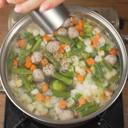 Когда все закипит, солим суп примерно половиной столовой ложки соли и перчим черным молотым перцем.