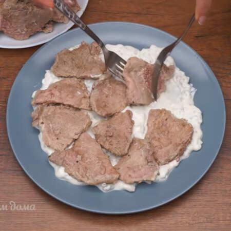 Сверху на соус выкладываем подготовленное мясо в один слой.