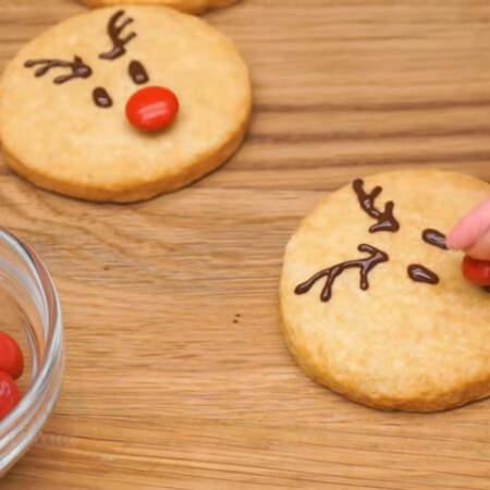 Ставим шоколадную точку где будет нос и сразу же прикрепляем красную конфетку. Я использовала конфеты M&M's.