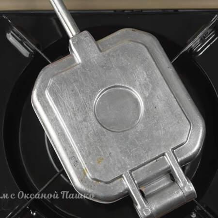 Форму закрываем и ставим на небольшой огонь. Готовим печенье постоянно переворачивая формочку.