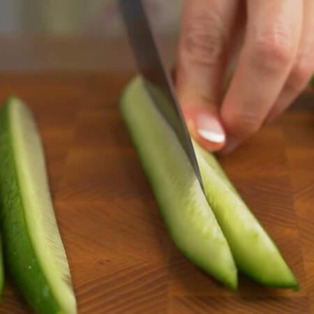 Длинный огурец разрезаем вдоль пополам, а затем одну из половинок разрезаем вдоль еще на 4 длинных кусочка.