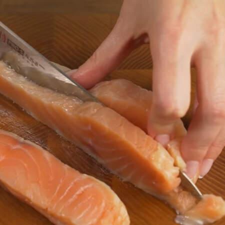 Берем кусок красной соленой рыбы и нарезаем его длинными пластинками шириной около сантиметра.