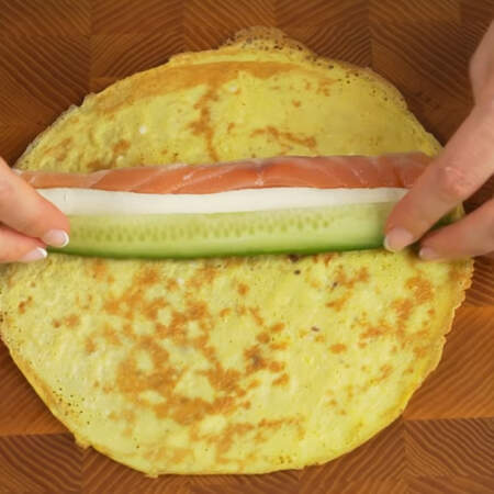 Складываем закуску. На яичный блин кладем длинный кусочек красной рыбы. Сбоку от красной рыбы выдавливаем по всей длине блина сливочный сыр.  Кладем подготовленный огурец.