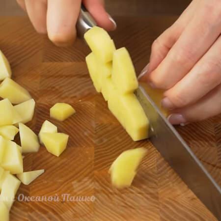 Пока варится рыба подготовим остальные ингредиенты. 300 г очищенного картофеля нарезаем небольшими кусочками.