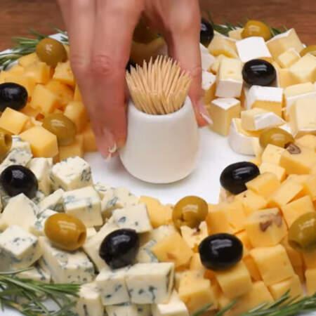 Сверху выкладываем оливки и маслины. Сырная тарелка Рождественский венок готова, можно подавать на стол.