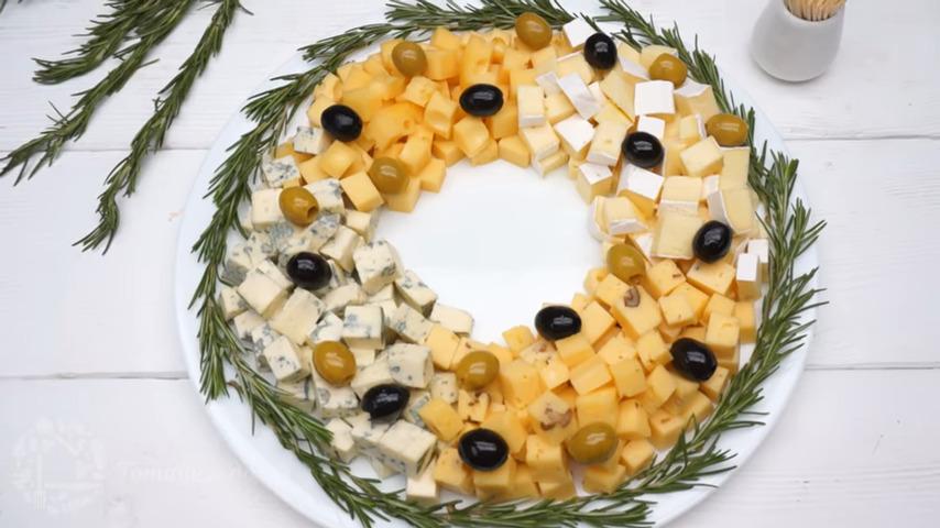 Такая сырная нарезка получается красивой и необычной. Готовится она очень просто и на столе выглядит нарядно и празднично. Такую тарелку с сырами можно приготовить за день до торжества и накрыть пищевой пленкой, чтобы сыры не заветривались.