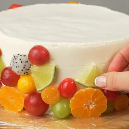 На готовый уже застывший торт приклеиваем подготовленные фрукты. Обратите внимание, что из под торта пищевую пленку вытаскивать не нужно. Фрукты размещаем так, чтоб они закрыли всю боковую часть торта.