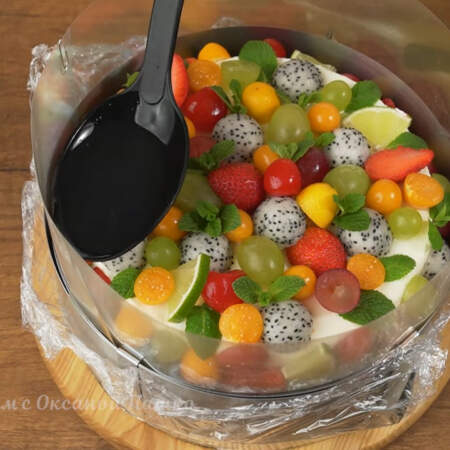 Аккуратно между тортом и кольцом заливаем приготовленное желе. Стараемся лить только по стеночке формы, чтобы не трогать фрукты, так как они могут отклеиться от торта.