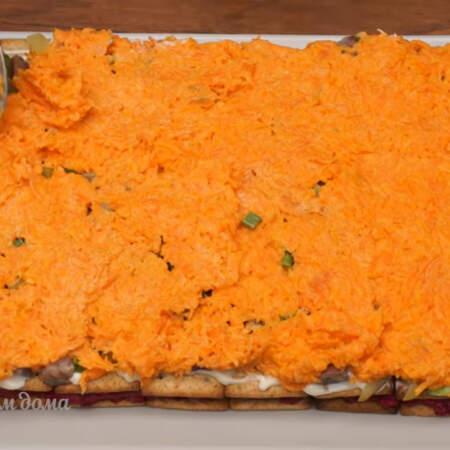 Выкладываем слой из подготовленной моркови и равномерно распределяем его по всей поверхности.