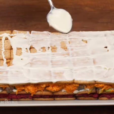 На морковный слой кладем слой из крекера. Крекер хорошо смазываем майонезом.