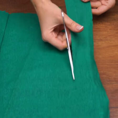 Берем гофро бумагу зеленого цвета и из нее будем нарезать зелень для букета, которой заполняем промежутки между кексами. Сначала из бумаги вырезаем длинные полоски шириной примерно 5-6 см.