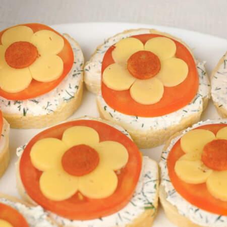 Обвалянные в паприке кружочки сыра аккуратно кладем в срединку каждого цветка.   Бутерброды готовы, можно подавать на стол.