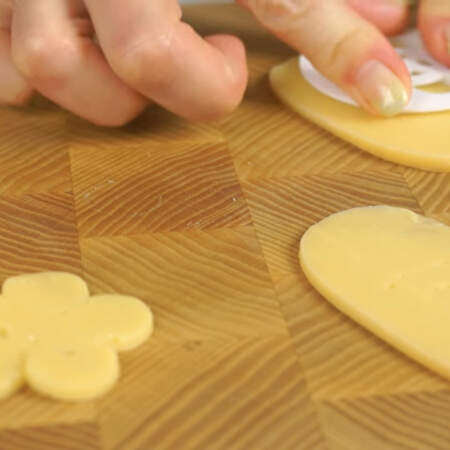 Берем формочку цветок и вырезаем из сыра цветы. Если нет такой формочки, можно сделать цветок из пяти кружочков.