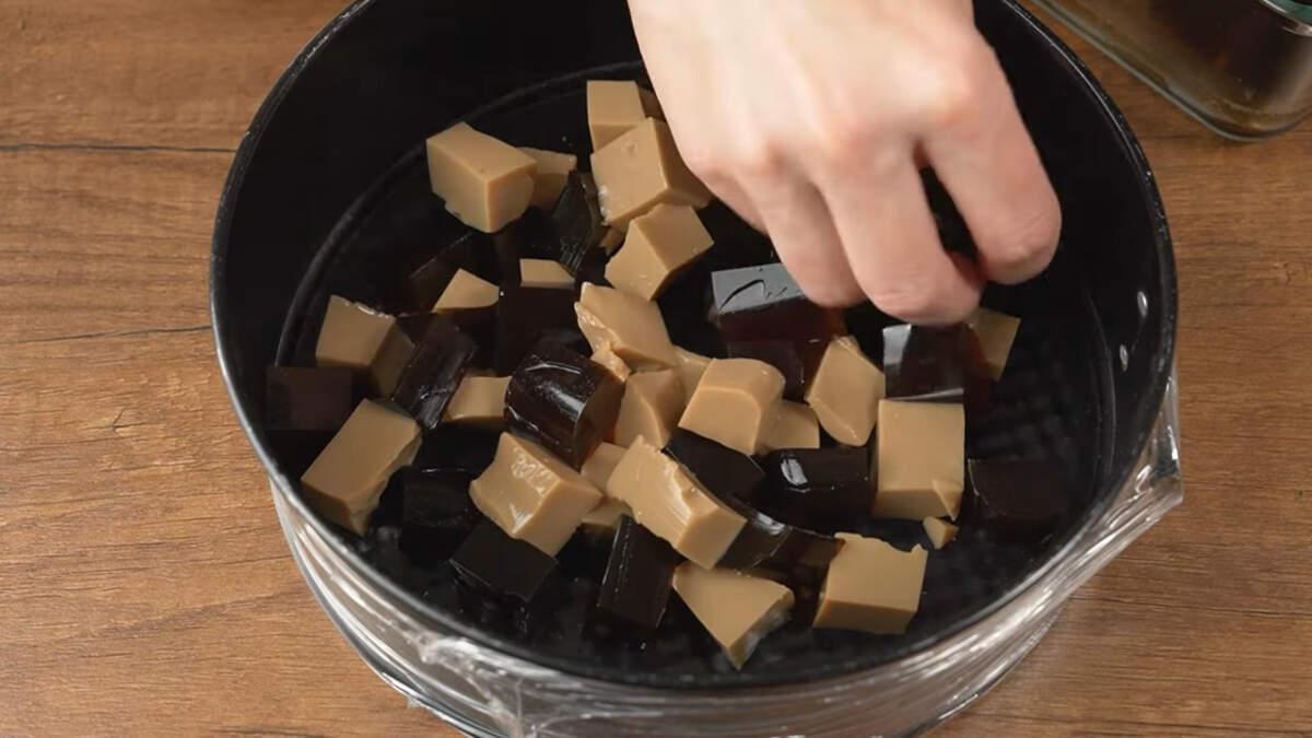 В подготовленную форму кладем кусочки желе. Стараемся выкладывать в перемешку. Часть желейных кубиков оставляем для украшения торта сверху.