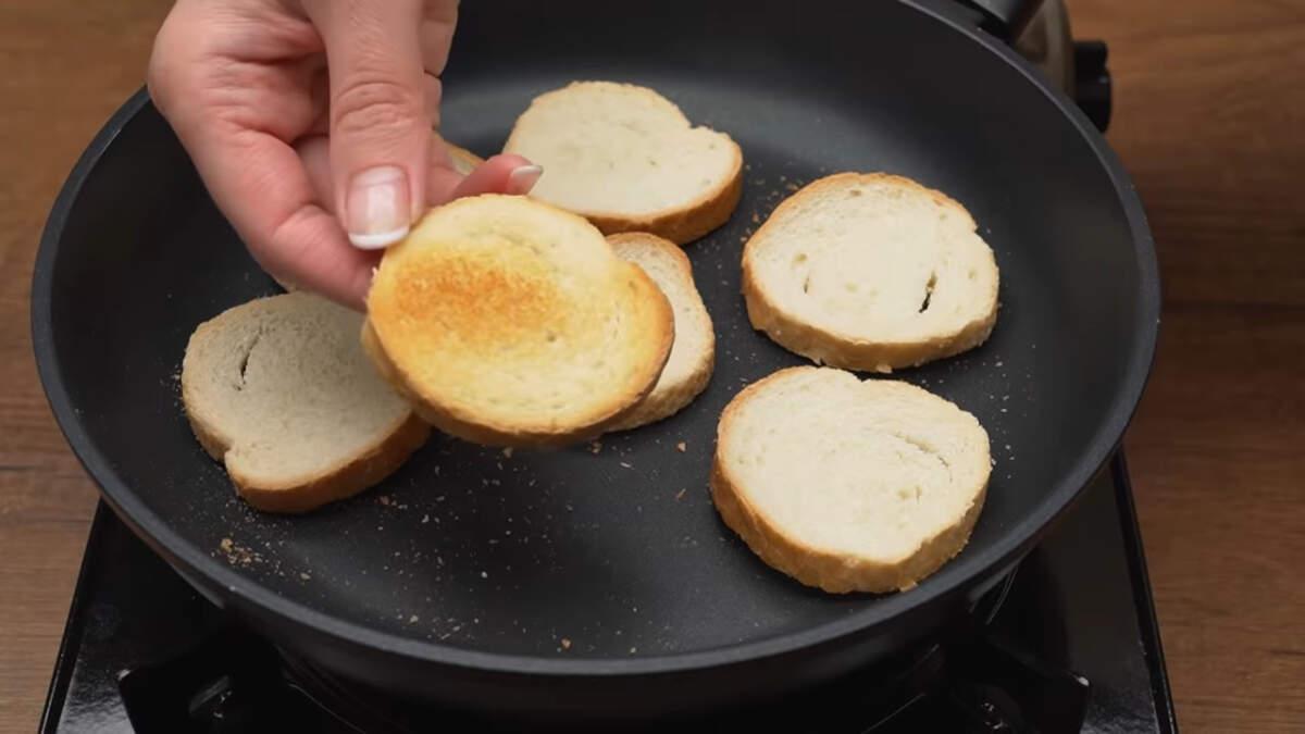Кусочки нарезанного батона кладем на разогретую сковороду. Обжариваем их на среднем огне с одной стороны до золотистого цвета. Также поджарить батон можно в тостере. Готовые гренки снимаем со сковороды.
