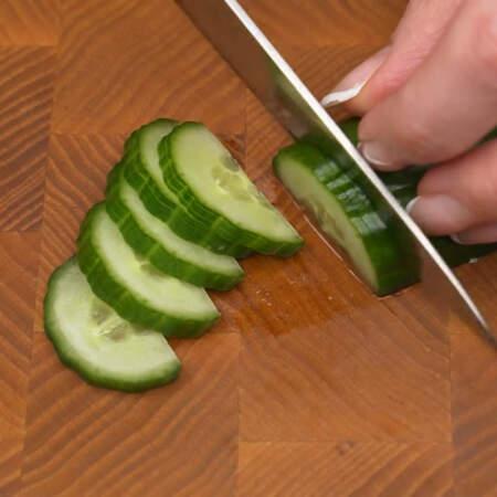 Огурец разрезаем вдоль пополам. Берем одну половинку огурца и делаем сначала 2 надреза не разрезая огурец полностью. Третьим резом отрезаем кусочек огурца полностью. Пластинки огурца нужно делать тонкими, чтобы они хорошо гнулись.