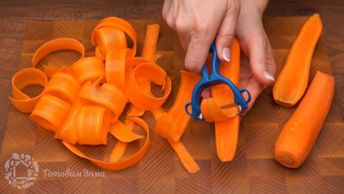 Пока настаивается торт приготовим украшения из моркови. Берем 2 уже очищенные моркови и овощечисткой срезаем с них ровные полосы. Срезать нужно настолько тонко, насколько позволяет овощечистка, ножом так нарезать морковку скорее всего не получится. Морковь для розочек нужно брать достаточно длинную и примерно одинаковой толщины по всей длине.