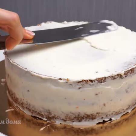Сверху торт обмазываем оставшимся кремом. По бокам кладем меньше крема, а на верх торта накладываем больше и выравниваем его шпателем или длинным ножом.