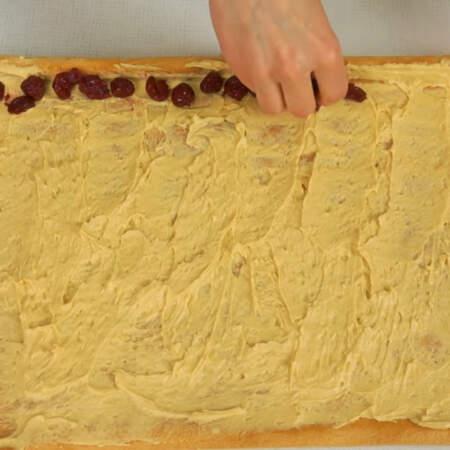 По краю бисквита выкладываем начинку. У меня это вишня.
