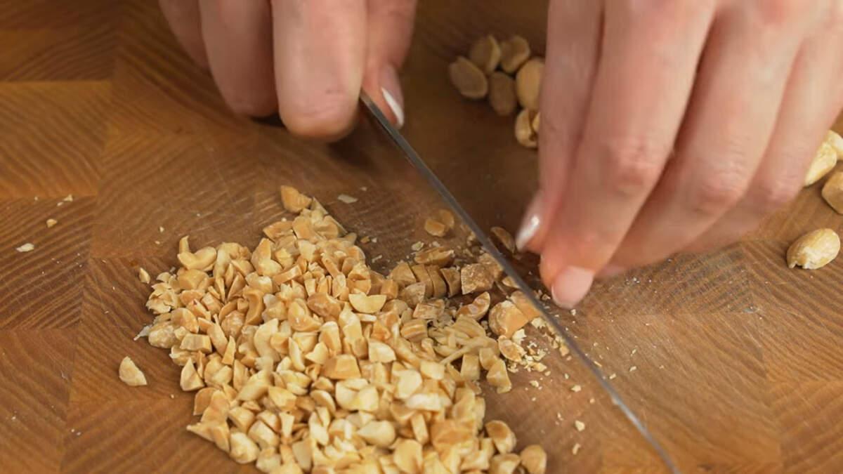 Пока остывает крем подготовим орехи. 100 г жаренного арахиса рубим ножом на небольшие кусочки. Вместо арахиса можно использовать и другие орехи, например грецкие, фундук, миндаль или фисташки.