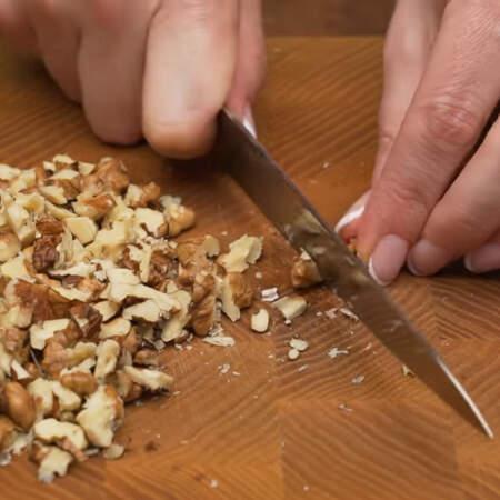 Сначала приготовим основу для торта. 60 г грецких орехов измельчаем ножом на более мелкие кусочки.