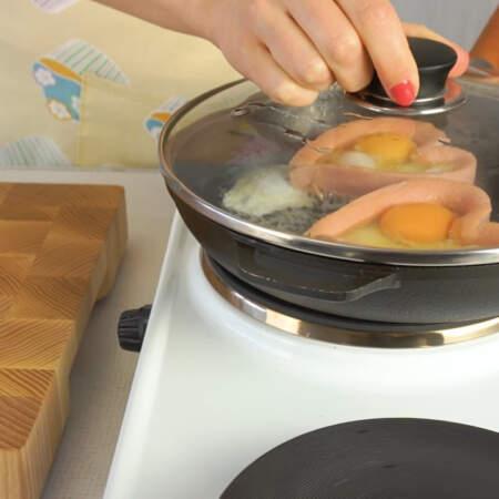 Сковороду накрываем крышкой и жарим яйца на маленьком огне до готовности.