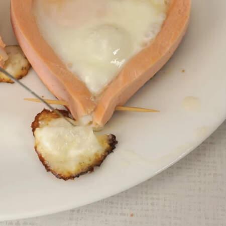 Готовую яичницу снимаем со сковороды и выкладываем на тарелку. Вытекший белок отрезаем и вынимаем зубочистки.
