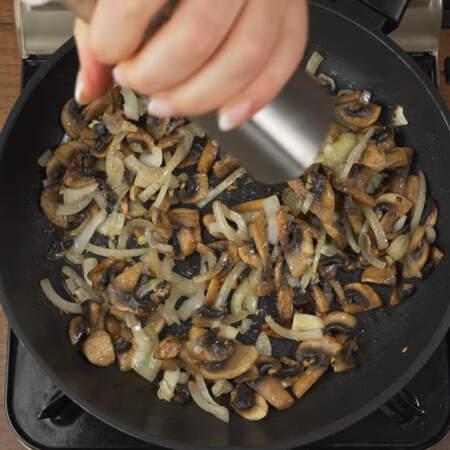 Обжариваем лук с грибами до золотистости лука. В конце грибы солим и перчим черным молотым перцем. Все перемешиваем и снимаем с огня.