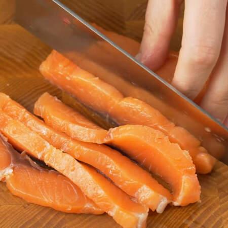 Сначала подготовим все ингредиенты для салата. 200 г красной соленой рыбы сначала нарезаем пластинками,