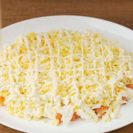 Слой с яйцами немного солим и наносим сеточку из майонеза.