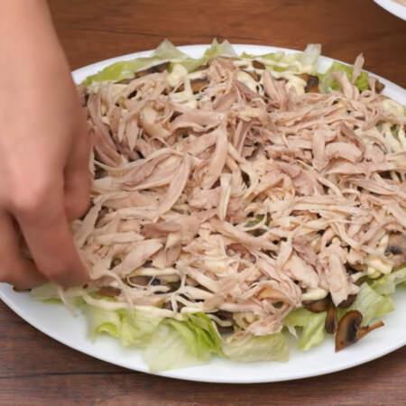 Следующим слоем кладем куриное мясо и равномерно распределяем его по поверхности салата.
