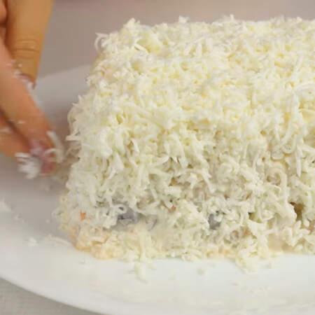 Тертыми белками посыпаем весь салат сверху и по бокам.